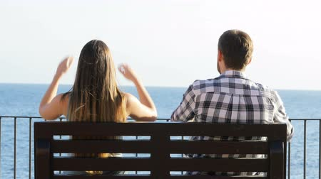 destino : Back view of a happy couple sitting on a bench and relaxing contemplating ocean
