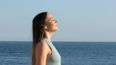 álmodozó : Side view portrait of a happy woman relaxing breathing fresh air on the beach