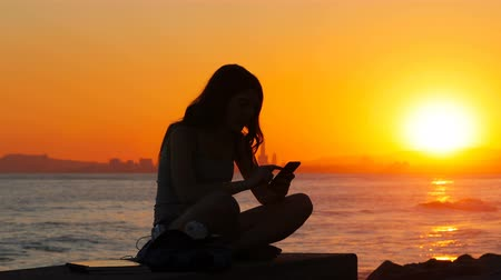 grants : Silhouette of an excited student reading good news on a smart phone at sunset on the beach