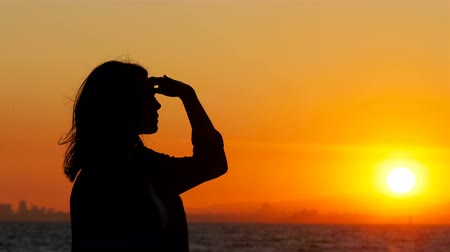 külvárosok : Silhouette of a woman scouting at sunset on the beach