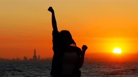 esteem : Silhouette of an excited woman jumping at sunset celebrating success on the beach Stock Footage