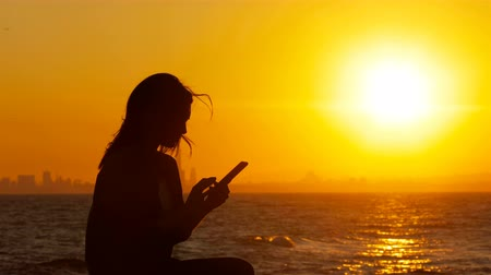 grants : Silhouette of an excited woman at sunset checking news phone on the beach