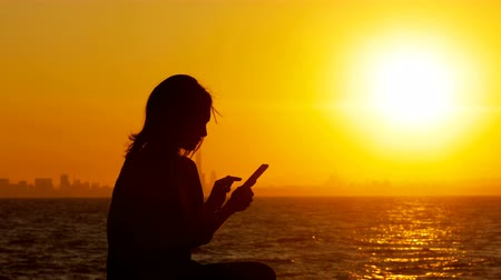 viagens de negócios : Silhouette of a woman using smart phone sitting on a bench at sunset Stock Footage