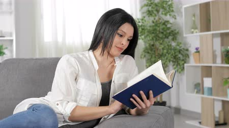 ders kitabı : Relaxed woman reading a book lying on a couch at home