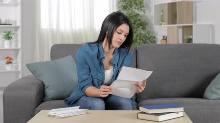 grants : Excited woman reading good news in a letter sitting on a couch at home