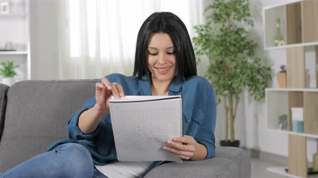 estudioso : Happy student reading notes on a laptop sitting on a couch in the living room Stock Footage