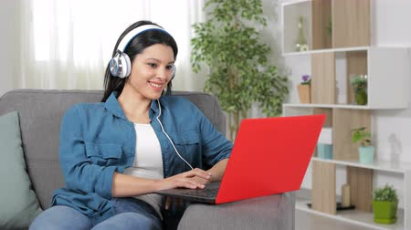 wearing earphones : Happy woman wearing headphones browsing laptop sitting on couch at home