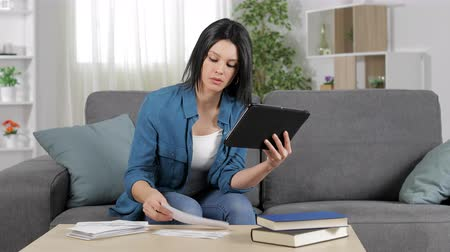 organizing : Concentrated woman checking bank receipts online sitting on a couch at home
