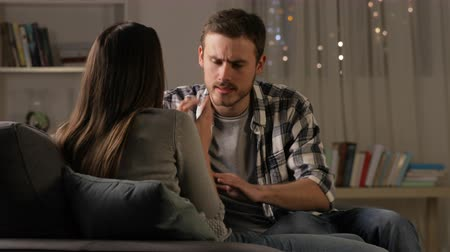 cheated : Angry man breaking up with his girlfriend on a couch in the night at home Stock Footage