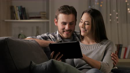 gives : Happy couple watching online streaming videos on a tablet sitting on a couch in the night
