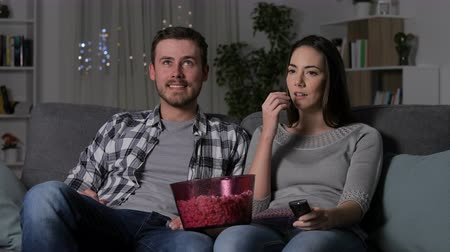 karartmak : Confused couple suffering from blackout watching tv sitting on a couch in the living room in the night at home Stok Video