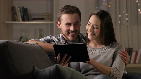 family watching tv : Happy couple in the night browsing tablet sitting on a couch at home