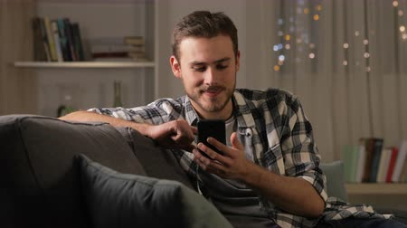 širokopásmové : Happy man using smart phone sitting on couch in the living room in the night at home