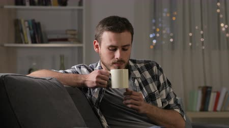 infused water : Happy man drinking tea and relaxing sitting on couch in the living room in the night at home Stock Footage