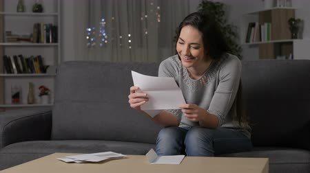 refund : Amazed woman reading good news on a letter sitting on a couch in the night at home