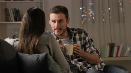 atender : Happy couple talking and drinking coffee sitting on couch in the night at home