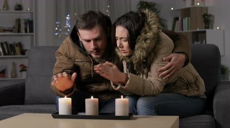 karartmak : Angry couple getting cold at home suffering a power outage sitting on a couch in the night