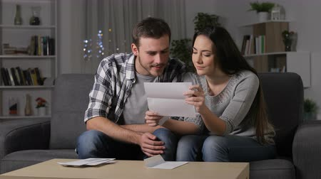 litera : Amazed couple receiving good news on a letter sitting on a couch in the night at home