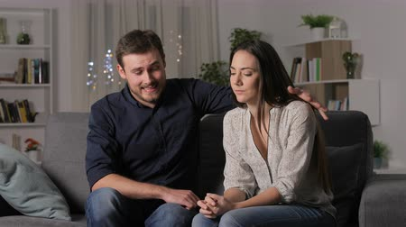 refusing : Woman rejecting boy at first date sitting on couch in the night at home Stock Footage