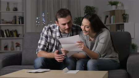 tebliğ : Excited couple receiving good news on letter sitting on couch in the night at home Stok Video