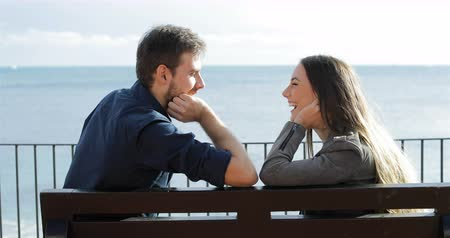 gives you : Profile of a happy couple looking at each other on a bench on the beach Stock Footage