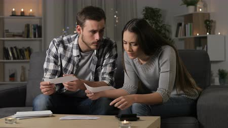 tebliğ : Sad couple checking bank receipts sitting on couch in the night at home