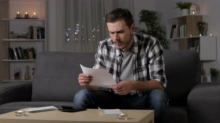 karartmak : Single sad man complaining reading a letter sitting on a couch in the night at home Stok Video