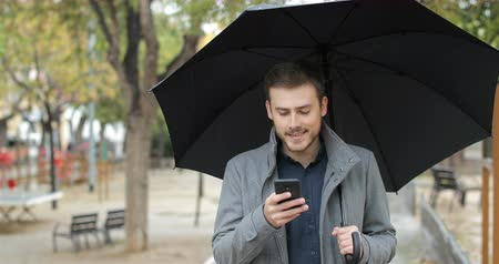 verificar : Disappointed man receiving wrong phone message in the rainy day walking in the street