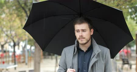 fraco : Melancholic man walking in a park a rainy day under a black umbrella