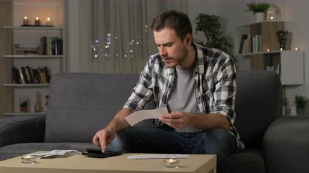 karartmak : Sad man accounting checking receipts sitting on a couch in the night at home