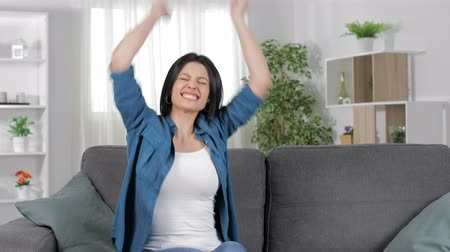 grants : Excited lady celebrating success alone sitting on a couch in the living room at home