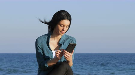scandal : Amazed woman posing on smart phone sitting on bench on the beach Stock Footage