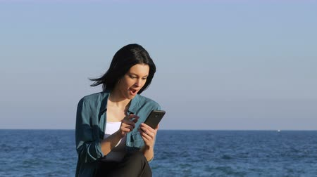 grants : Excited woman finding good news on smart phone sitting on bench on the beach Stock Footage