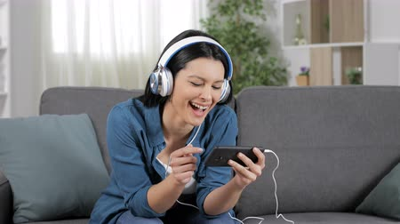 mobile music : Funny woman watching videos on smart phone sitting on couch in the living room at home