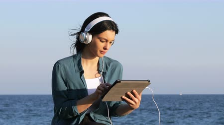 dinleme : Serious woman browsing and listening tablet content on the beach Stok Video