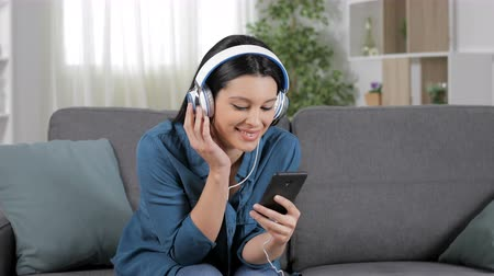 listens : Happy woman listening to music from cell phone sitting on couch in the living room at home Stock Footage