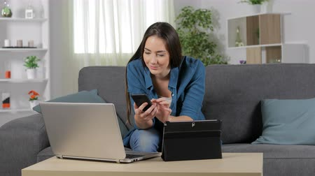 širokopásmové : Excited woman using multiple devices sitting on couch at home