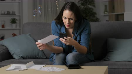 grants : Angry woman claiming wrong receipt on phone sitting on couch in the night at home