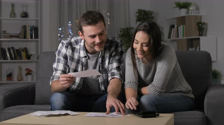 tebliğ : Happy couple checking checking receipts using a calculator sitting on a couch in the night at home