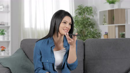 žádost : Happy woman using phone voice recognition recording on smart phone sitting on couch at home
