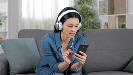 vay : Surprised woman listening to music from cell phone sitting on couch at home
