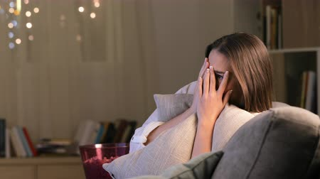 watch tv : Single scared woman watching horror movie on tv sitting on a couch at home in the night