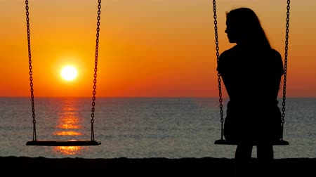 luto : Back view silhouette of a sad girl swinging looking at side on an empty seat on the beach at sunset