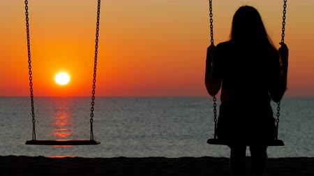 özlem : Back view of a girl swinging at sunset on the beach contemplating sun