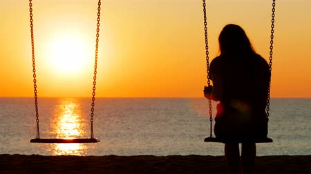concerned girl : Back view portrait of a sad girl silhouette swinging at sunset on the beach