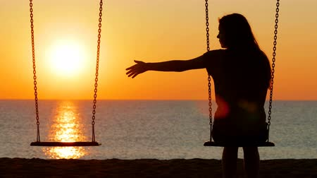 özlem : Back view silhouette of a sad girl at sunset missing her partner on a swing on the beach Stok Video
