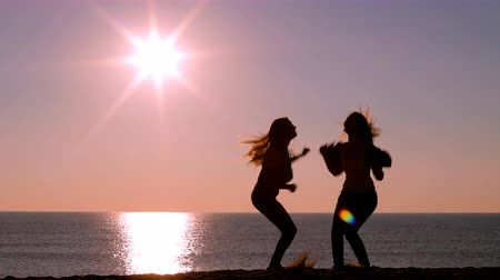 esteem : Full body of two excited friends jumping raising arms at sunrise on the beach