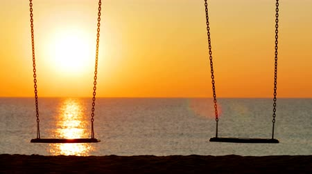без вести пропавшие : Empty swing at sunset on the beach with the sun in the background
