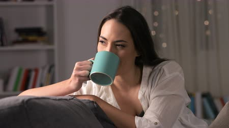chill out : Happy woman drinking coffee sitting on couch at home in the night Stock Footage