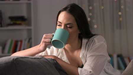 Serious pensive woman drinking coffee sitting on couch at home in the night